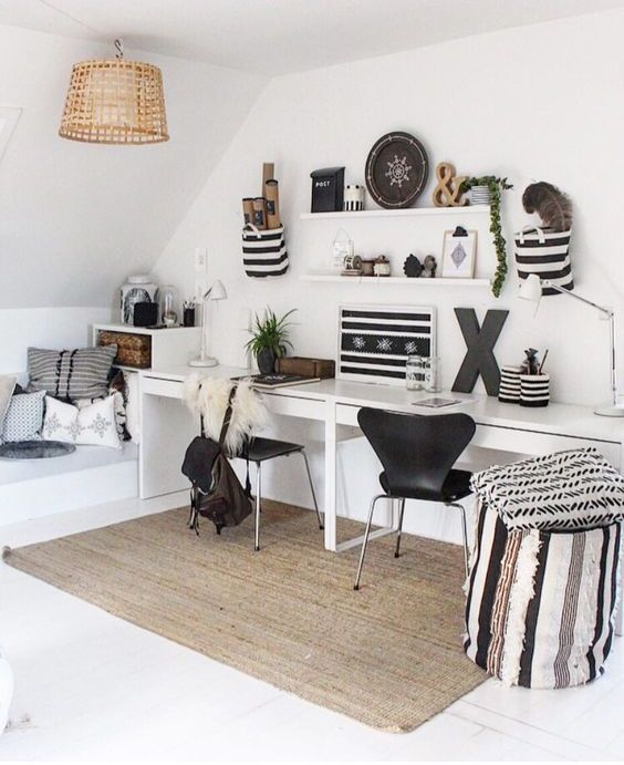 a chic attic Scandinavian home office with a shared desk, black chairs, a couple of shelves, artworks and objects on display