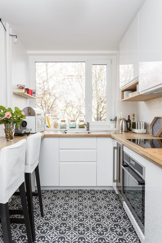 a chic contemporary U-shaped kitchen with sleek white cabinets, butcherblock countertops, a mosaic tile floor and white stools