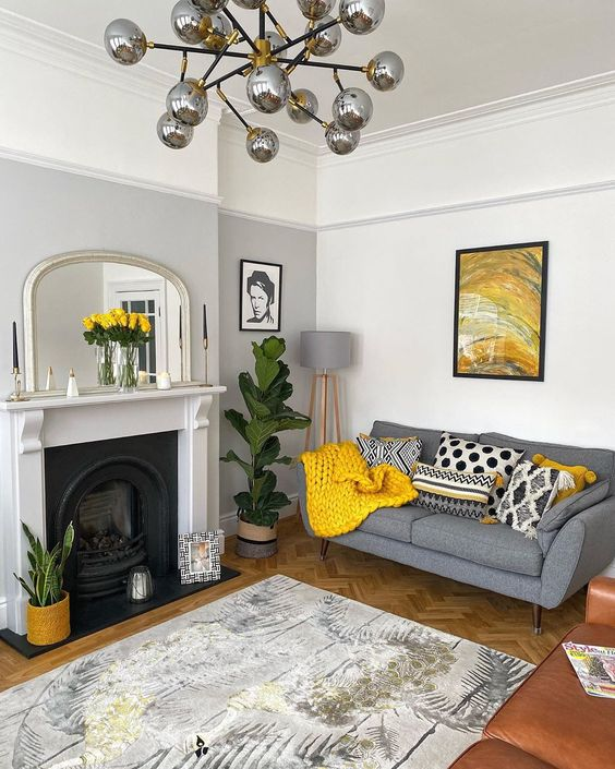 a chic living room with a grey accent wall, a fireplace, a grey sofa with printed pillows, a bold artwork and a rug