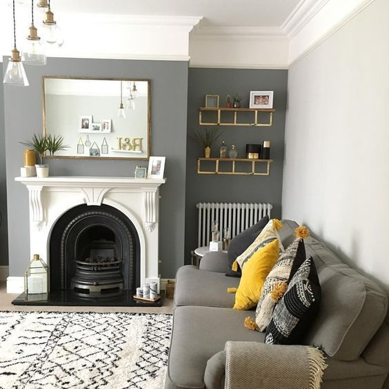 a chic living room with a grey accent wall, grey furniture, a fireplace, some shelves, printed textiles and pendant lamps