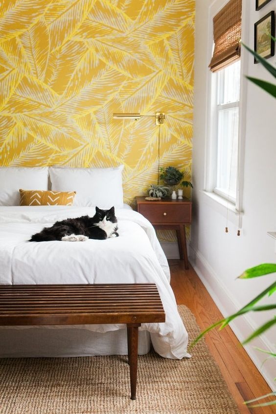 a chic mid-century modern bedroom with a feather print accent wall, dark stained wooden furniture and gold touches
