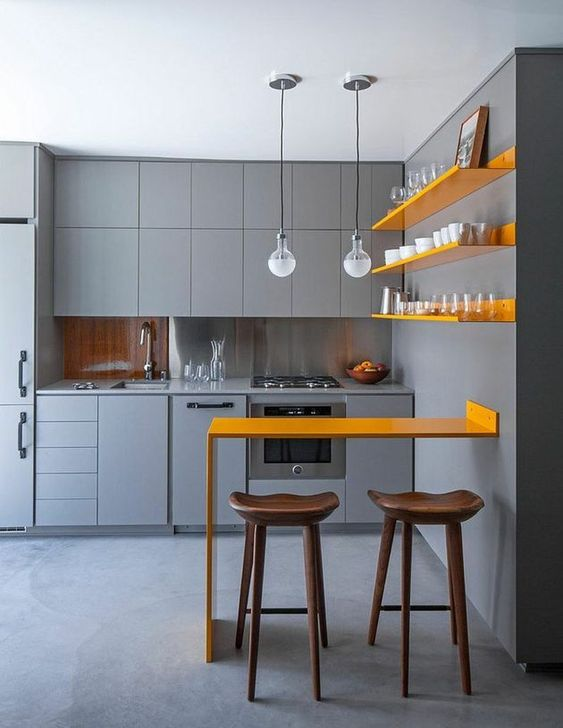 a chic minimalist kitchen with matte grey cabinetry, sunny yellow shelves and a matching counter for meals and drinks