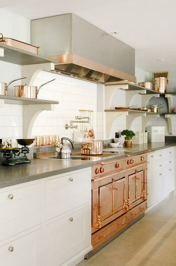 a chic one wall kitchen with white cabinets, grey stone countertops, a copper cooker, a grey and copper hood is wow