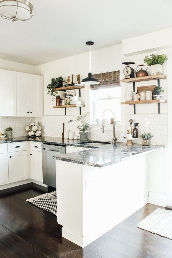 a chic white U-shaped kitchen with elegant cabinets, grey stone countertops, open wooden shelves and potted greenery