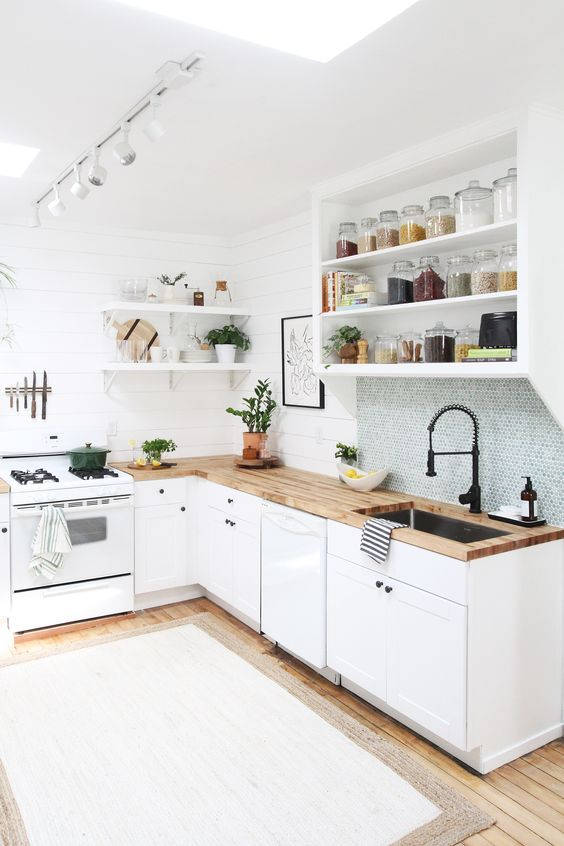 a chic white kitchen with lower cabinets and an open cabinet plus open shelves, butcherblock countertops and a blue penny tile backsplash