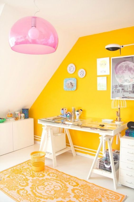 a colorful home office with a yellow accent wall, white modern furniture, bold artworks and prints, a yellow printed rug and a pink pendant lamp