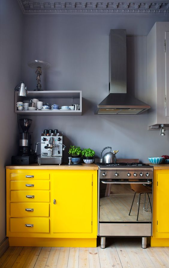 a colorful kitchen with graphite grey walls and upper cabinets, lower yellow ones and elegant appliances just wows