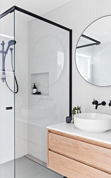 a contemporary Nordic bathroom with light grey tiles, a floating vanity, black touches and a round mirror