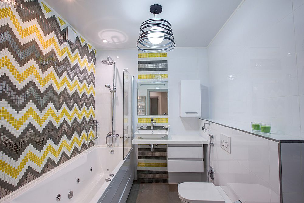 a contemporary and bright bathroom done in white, grey and yellow, with pretty mosaic tiles done with chevron and stripes