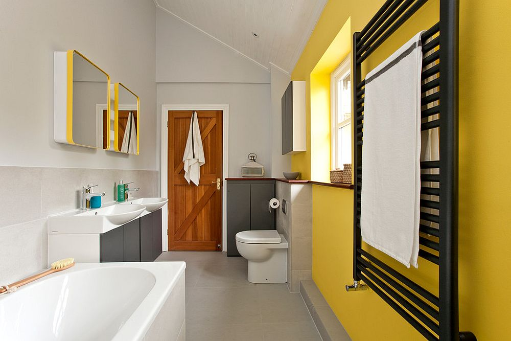 a contemporary bathroom with a yellow accent wall, grey and white cabinets, yellow framed mirrors and other touches