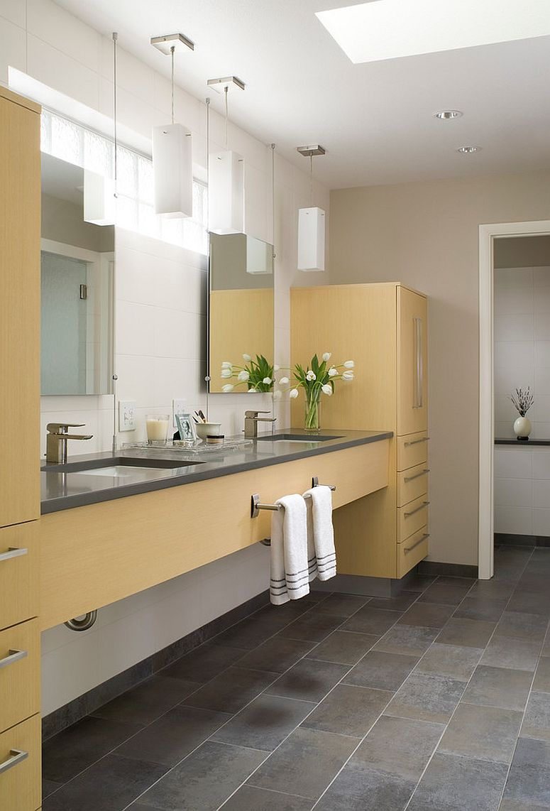 a contemporary bathroom with neutral walls, grey tiles on the floor, a large yellow storage unit and pendant lamps