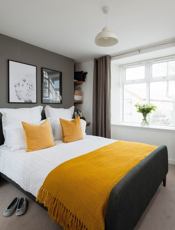 a contemporary bedroom with white walls and a grey accent one, an upholstered grey bed, mustard bedding, a gallery wall and a pendant lamp