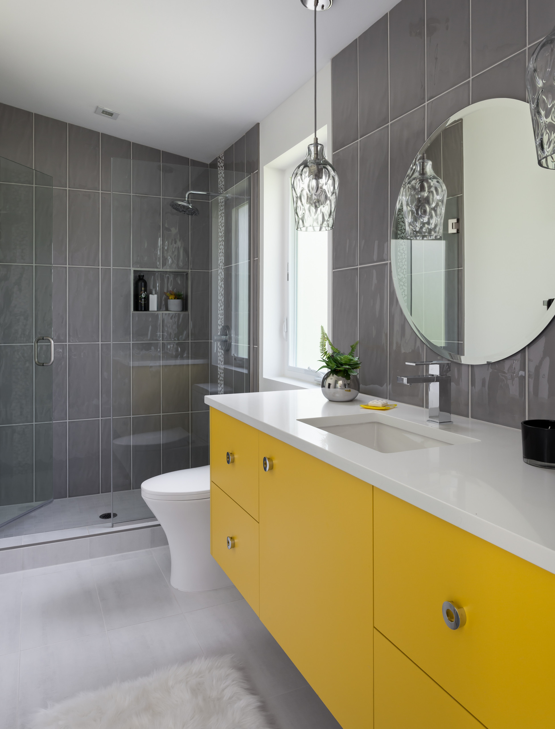 a contemporary grey bathroom with a bold yellow vanity, some pendant lamps and white countertops plus a round mirror