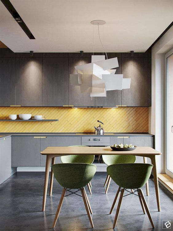 a contemporary kitchen with grey cabinetry of different shades, a yellow skinny tile backsplash and green chairs