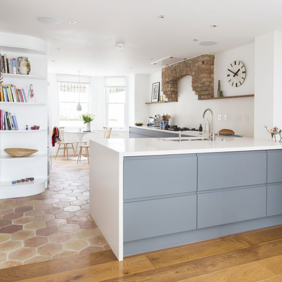 a contemporary kitchen with sleek grey and white cabinets, a brick hood and a small dining space by the window