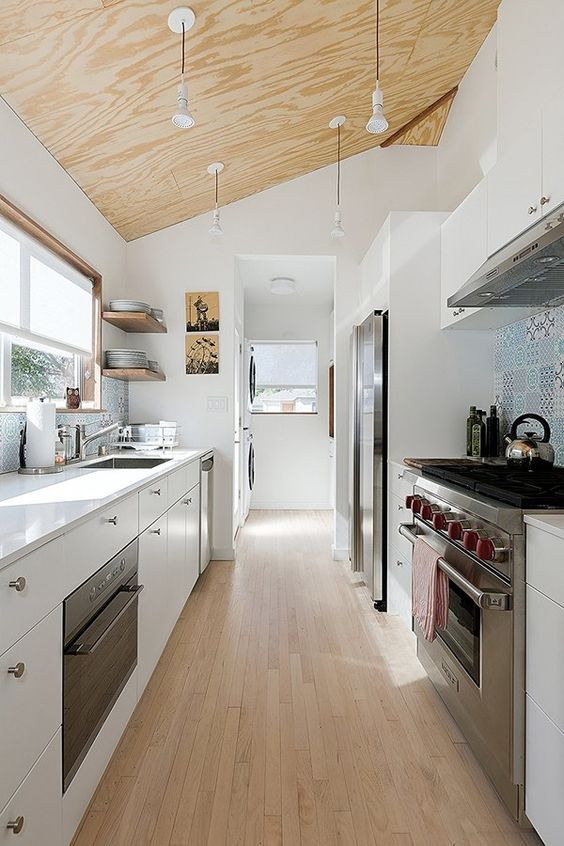 a contemporary white galley kitchen with a plywood ceiling with pendant lamps a wooden floor and a blue tile backsplash