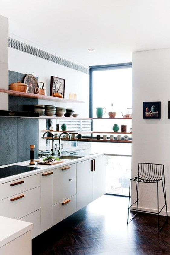 a contrasting L-shaped kitchen with white cabinets, a concrete backsplash, open shelves, a metal stool and pretty porcelain