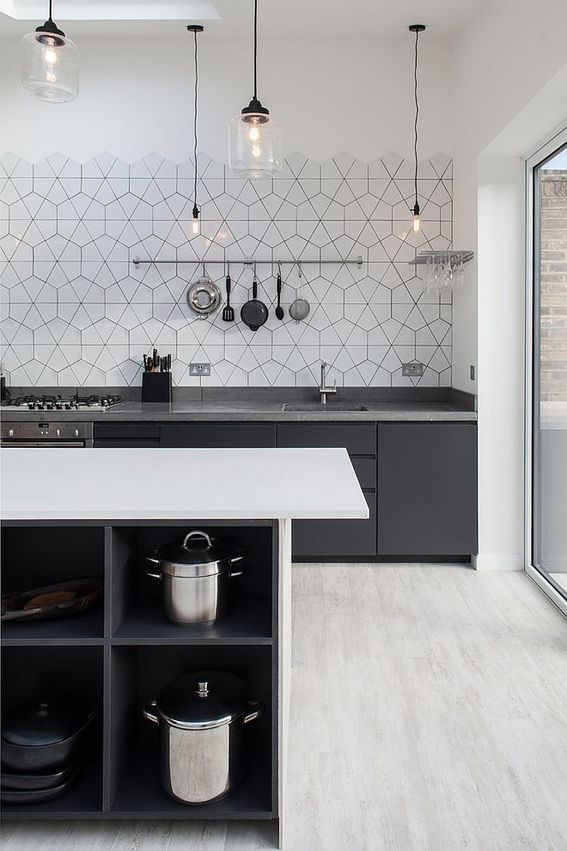 a contrasting Scandinavian kitchen in black, grey and white, black cabinets with grey countertops, a white kitchen island and hex tiles
