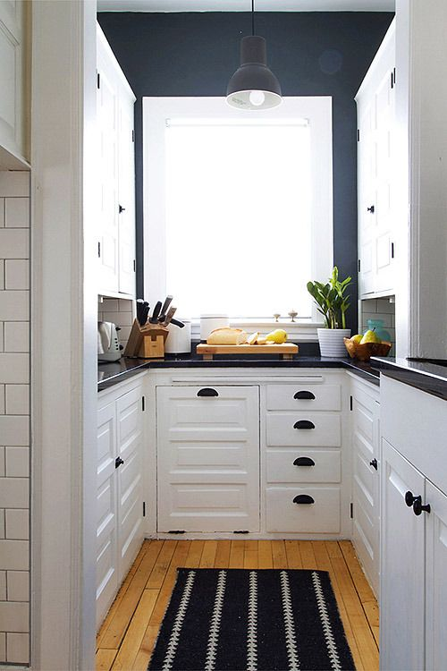 a contrasting U-shaped kitchen with white cabinetry, navy walls, black fixtures and black countertops is super chic