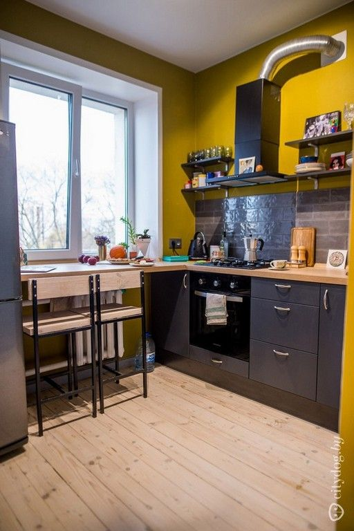 a contrasting kitchen with graphite grey cabinetry and a tile backsplash, mustard walls and wooden countertops looks unusual