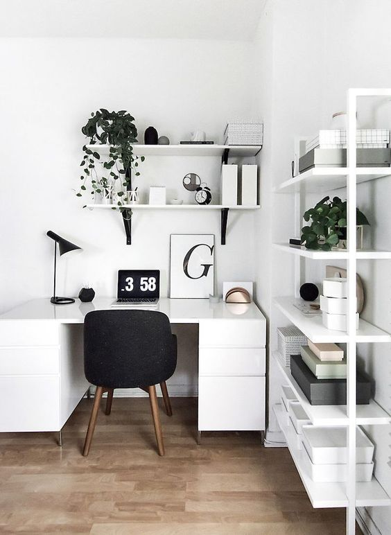 a cool Scandinavian home office with a white desk, a large shelving unit, potted greenery, black chairs and touches of black