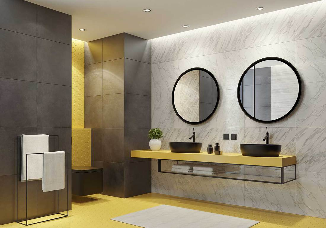 a cool bathroom with a white marble and grey tile wall, a floating yellow vanity, a couple of mirror and a bold yellow floor