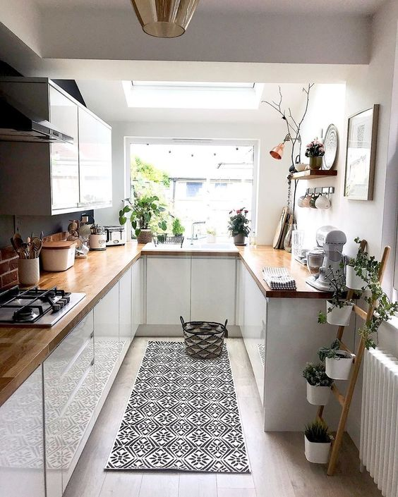 a cool contemporary U-shaped kitchen with sleek white cabients, butcherblock countertops, a bold rug and potted plants