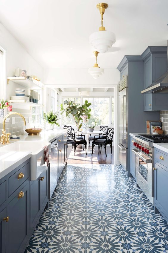 a cool modern blue kitchen with a printed tile floor, white countertops, gold fixtures and elegant pendant lamps