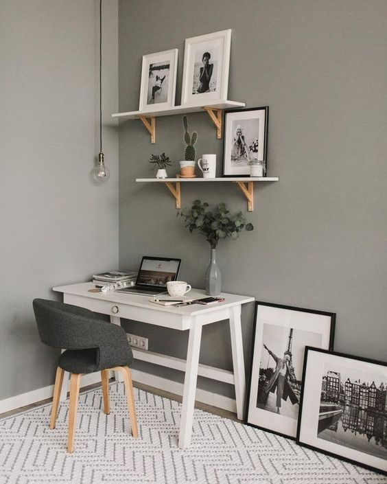a cozy Scandinavian home office with grey walls, a small white desk, a grey upholstered chair, shelves and artworks