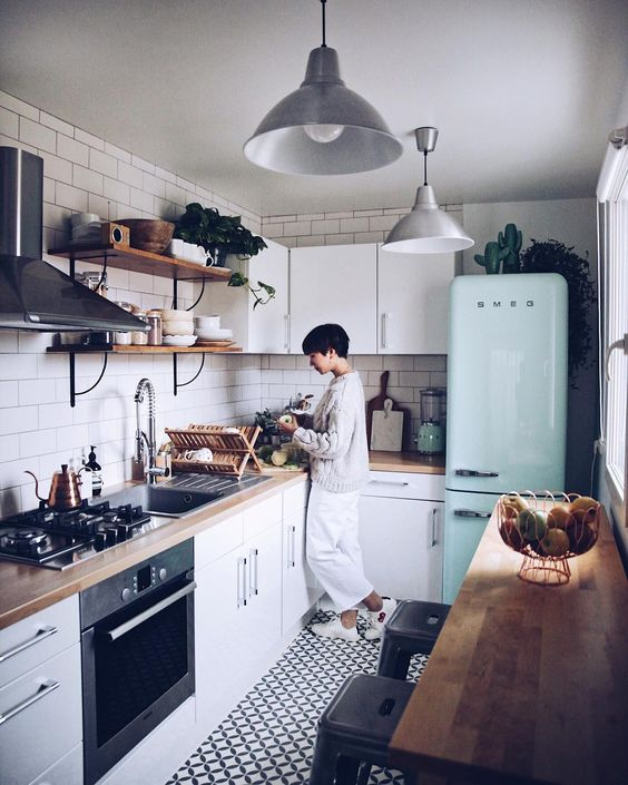 a cozy farmhouse kitchen with white cabinets, a white subway tile backsplash, a mint fridge and a long table for breakfasts
