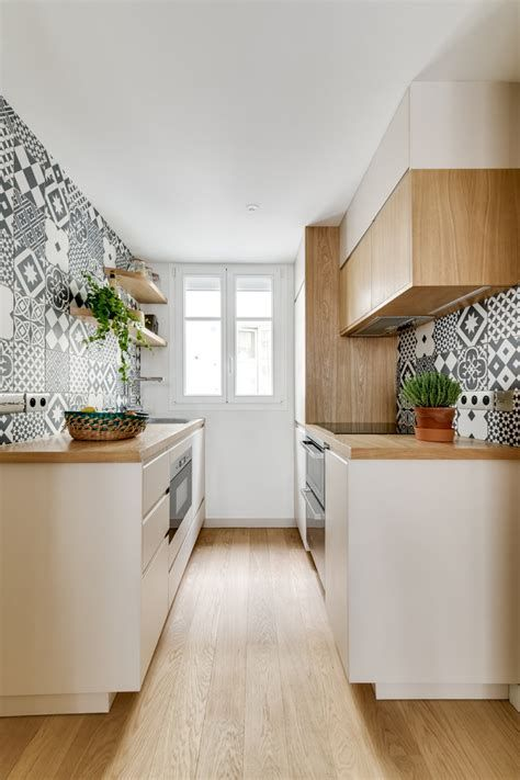 a cozy modern galley kitchen with white cabinets, wooden countertops, black and white printed tiles on the walls