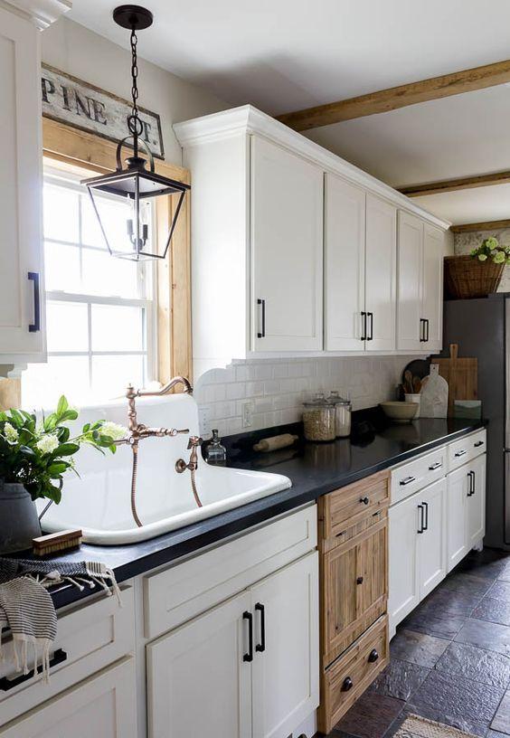 a cozy white farmhouse kitchen with black countertops, a white tile backsplash, black fixtures, a black pendant lamp