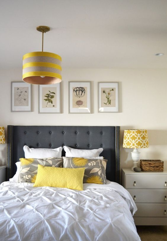 a creamy bedroom with a gallery wall, neutral nightstands, grey and yellow bedding, a striped lamp and a printed one