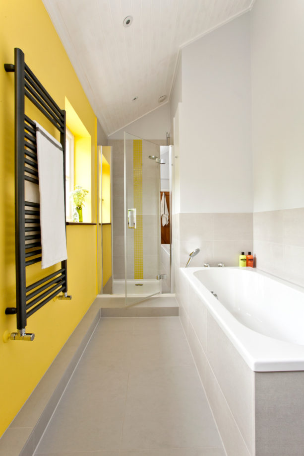 a dove grey bathroom with a bold yellow accent wall, a small shower zone and a black radiator looks stylish
