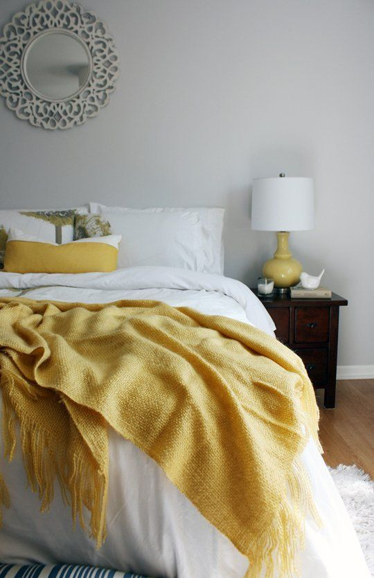a dove grey bedroom with a dark nightstand, a bed with yellow and white bedding and a mirror in a carved frame