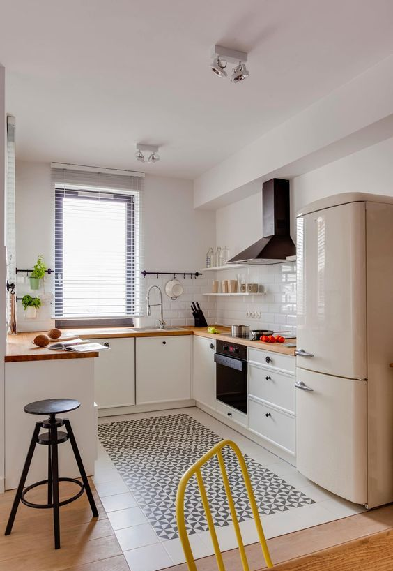 a fabulous contemporary kitchen with white cabinets, butcherblock countertops, black touches and a neutral fridge