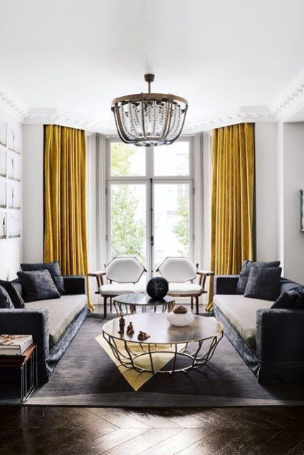 a fabulous living room with white walls and a ceiling, grey sofas, yellow curtains, a chic loveseat, a refined chandelier and coffee tables