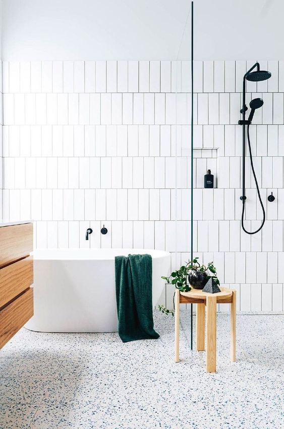 a fresh Scandinavian bathroom with white skinny tiles, a terrazzo floor, a floating vanity and black fixtures