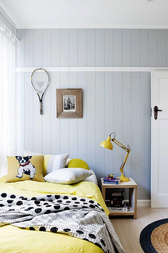 a fun bedroom with grey beadboard walls, a bed with grey and yellow bedding, whimsy wall decor and a yellow lamp