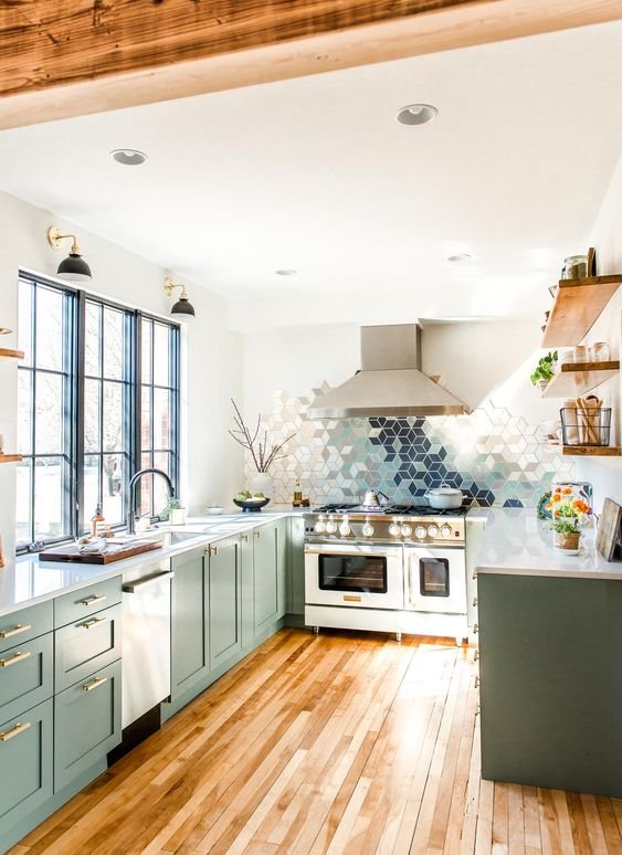 a gorgeous U-shaped kitchen green kitchen with only lower cabients, white stone countertops, a geometric tile backsplasj and wooden shelves