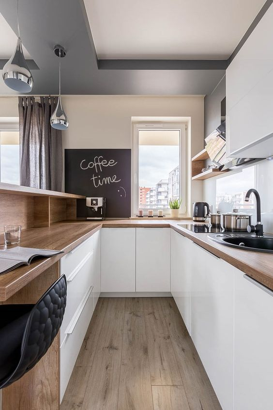 a gorgeous U-shaped kitchen with sleek white cabinets, butcherblock countertops, a chalkboard and black fixtures