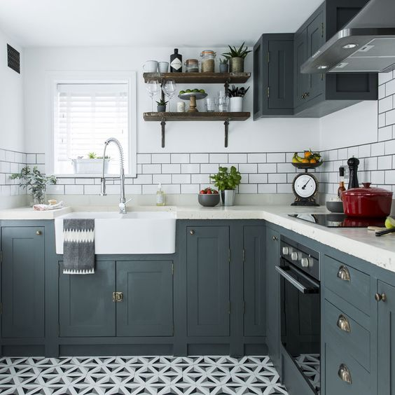 a graphite grey L-shaped kitchen, white subway tiles, white countertops and a printed mosaic floor is cool