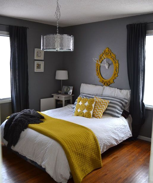 a graphite grey bedroom with white furniture, grey and mustard bedding and a mustard frame on the wall plus black curtains