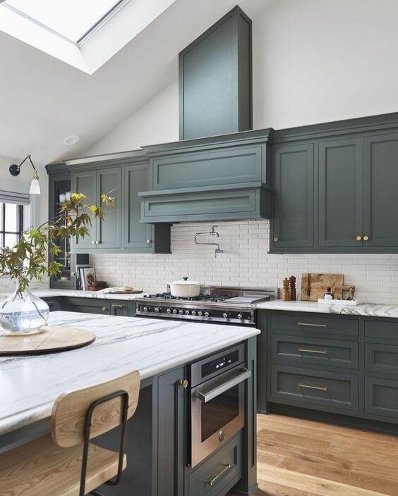 a graphite grey one wall kitchen with a white tile backsplash, white stone countertops and skylights over the space