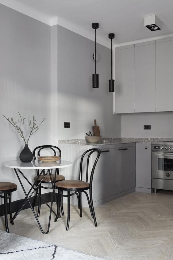 a grey Nordic kitchen with two tone cabinets, grey terrazzo countertops, a hairpin leg table and black chairs looks cool