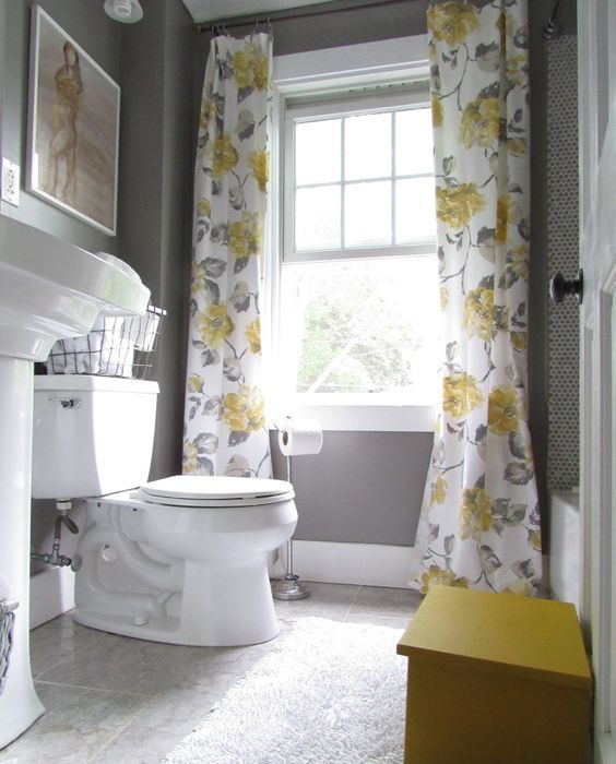 a grey bathroom with a grey marble floor, a yellow bench, yellow and grey floral curtains and some artworks