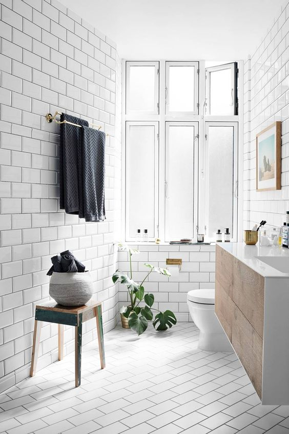 a light-filled Scandinavian bathroom clad with white subway tiles, a wooden floating vanity, wooden furniture and potted plants