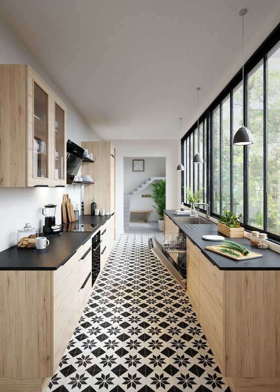 a light-stained plywood kitchen with black countertops, a glazed wall, black shelves and pendant lamps