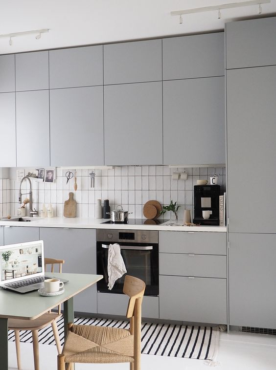 a lovely Nordic kitchen in grey, white skinny tiles, a striped rug, woven chairs is welcoming and very stylish