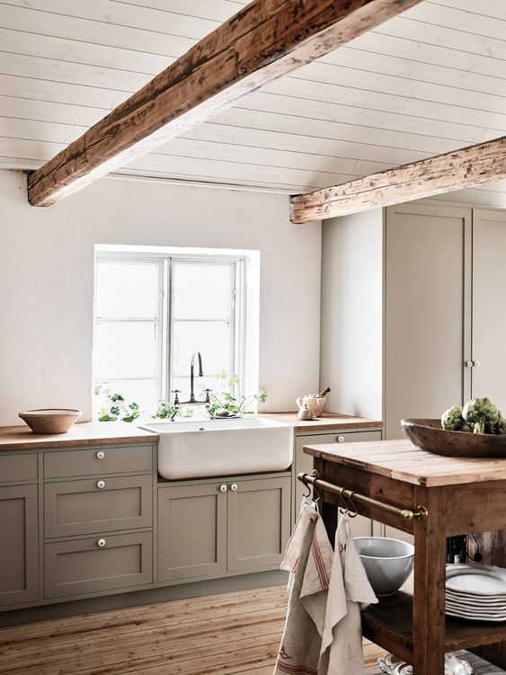 a lovely Scandinavian ktichen with a farmhouse feel, grey cabinets, wooden beams and a wooden kitchen island is wow
